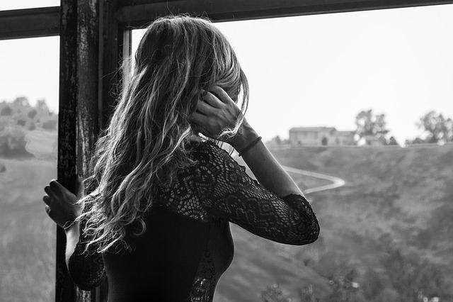 女性が窓から外を見ています